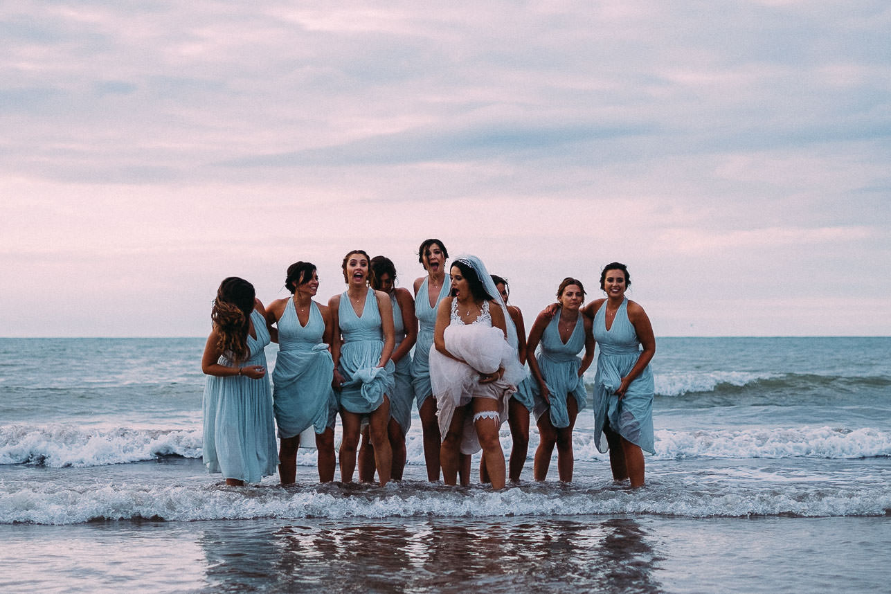 Fun and relaxed bride and bridemaids in the sea at a New Quay wedding, West Wales