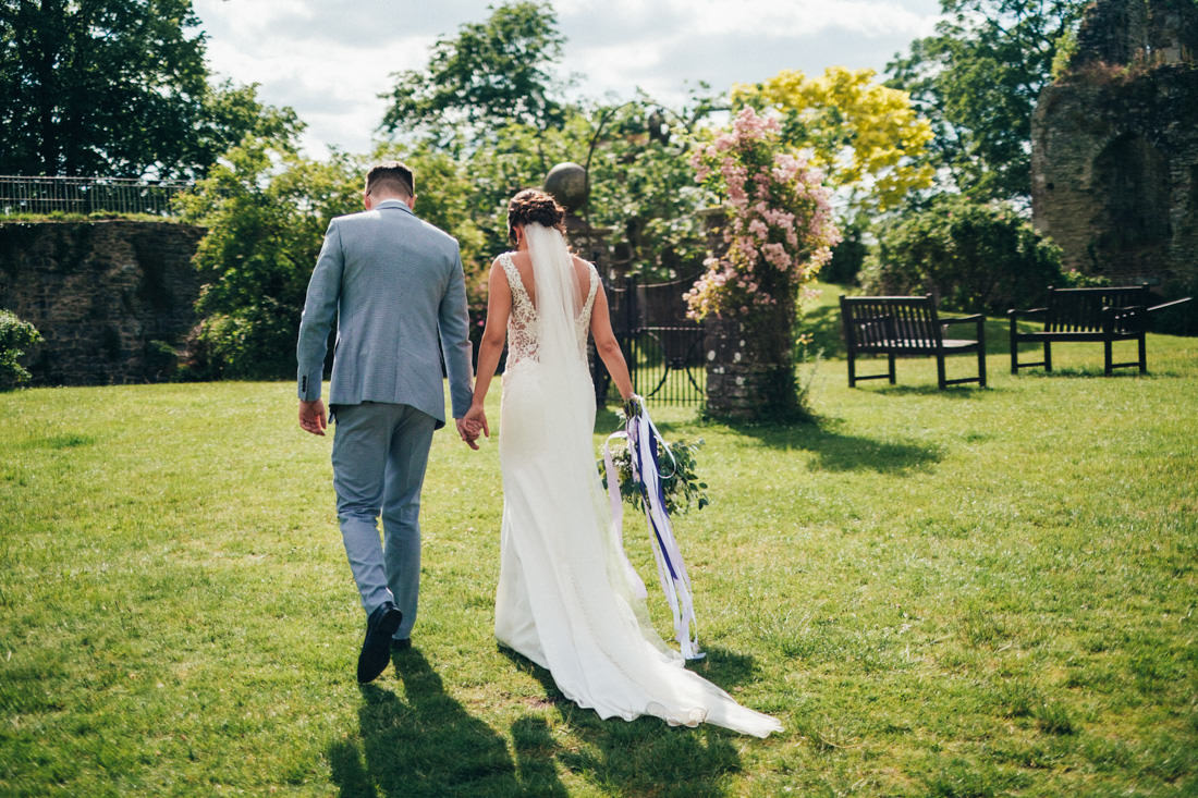 004 CANDID PORTRAIT OF BRIDE AND GROOM WALKING IN BEAUTIFUL DRESS USK CASTLE WEDDING PHOTOGRAPHY