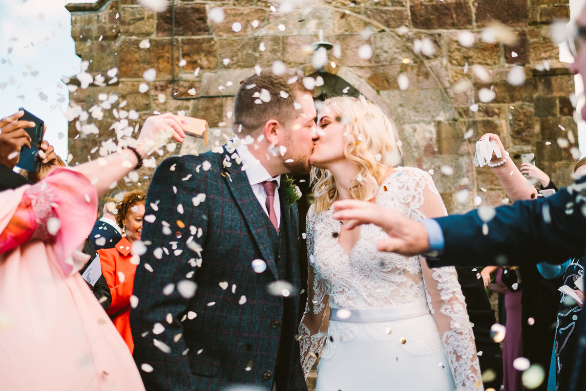 02 BRIDE AND GROOM KISS IN CONFETTI WEDDING EXIT LLANIDAN WEDDING ANGLESEY