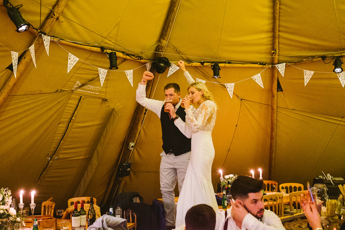 05 BRIDE AND GROOM STANDING ON CHAIRS DRINKING BEERS ON WEDDING DAY TROS YR AFON ANGLESEY