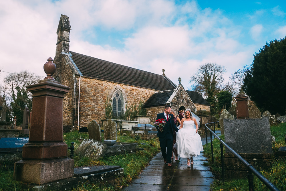 001 NEWLYWEDS MAKING THEIR EXIT WEDDING CEREMONY BRIDGEND CHURCH WEDDING PHOTOGRAPHY