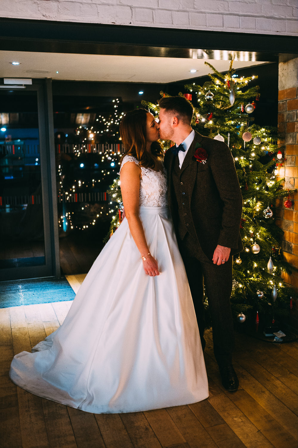003 BRIDE AND GROOM ROMANTIC MOMENT IN FRONT OF CHRISTMAS TREE WEDDING PHOTOGRAPHY SWANSEA NATIONAL WATERFRONT MUSEUM WEDDING