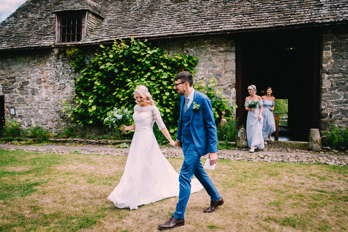 BRIDE AND GROOM WALKING BARN CEREMONY USK CASTLE WEDDING PHOTOGRAPHY