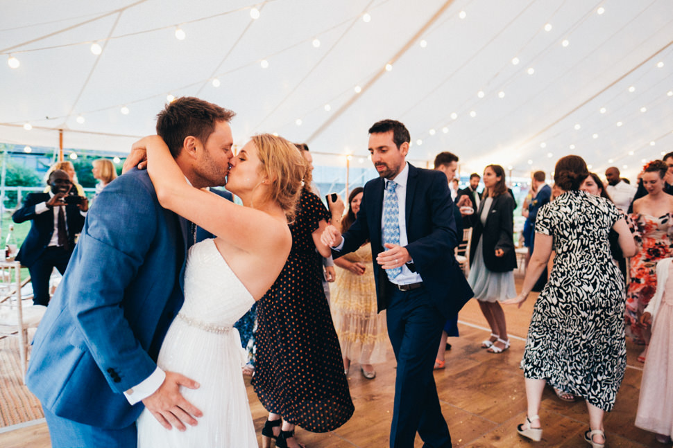 Candid moment of fun bride and groom first kiss after their first dance at marquee wedding at Humble by Nature Monmouthshire wedding photography
