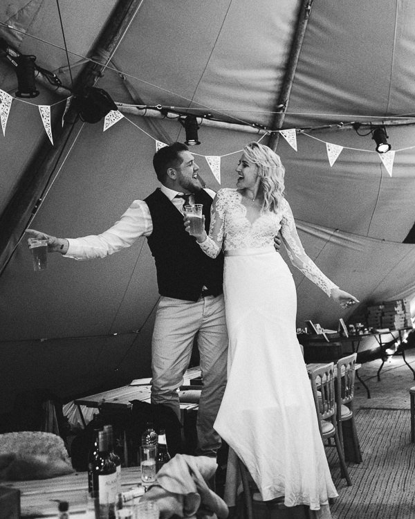Super fun bride and groom photo drinking pints standing on chairs at marquee wedding at Tros-yr-Afon, Beaumaris Anglesey wedding photography